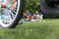 Casual family spending time in park at daytime, bicycle on foreground Royalty Free Stock Photo