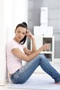 Casual girl in jeans and t-shirt sitting on floor Stock Photo