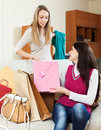 Casual girls together looking purchases from shopping bags at home Royalty Free Stock Images
