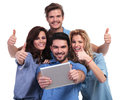 Casual group of people reading good news on their tablet pad computer and make the ok thumbs up sign white background Stock Image