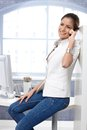 Casual happy businesswoman portrait of using mobile phone sitting on office desk in jeans Royalty Free Stock Photography