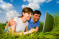 Casual happy couple on a laptop computer outdoors. Royalty Free Stock Photo