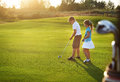 Casual kids at a golf field holding golf clubs sunset Stock Image