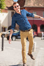 Casual man balancing in city young on one leg a and smiling to the camera Royalty Free Stock Image