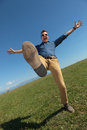 Casual man balancing outdoors young standing in a leg outdoor in the grass while holding his arms opened and screaming Royalty Free Stock Photography