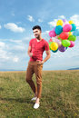 Casual man with baloons over his shoulder balloons Royalty Free Stock Photos