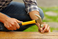 Casual man hammering nail in plank at home Royalty Free Stock Photo