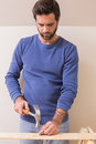 Casual man hammering nail in plank Royalty Free Stock Photo