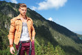 Casual man with hand in pocket in the mountains young posing outdoor a his and looking into camera Stock Images