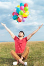 Casual man holds balloons with open arms young holding outdoor wide while looking up Royalty Free Stock Photo