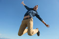 Casual man jumps in mid air young jumping outdoor and screaming with arms opened Stock Photography