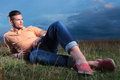 Casual man laying with feet crossed in the grass full length picture of a young outdoor his and looking away from camera Royalty Free Stock Photography