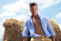 Casual man outdoor looks down with unbuttoned shirt young posing leaning on a haystack and looking at camera his Stock Photos