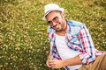 Casual man picking a flower from a field and smiles young to the camera Royalty Free Stock Images