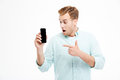 Casual man pointing finger on smartphone screen over white background Royalty Free Stock Photo