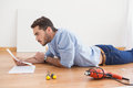 Casual man reading instruction manual for power tool at home in the living room Royalty Free Stock Photography