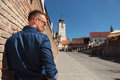 Casual man in sibiu back view of a young standing next to a brick wall city romania near the council tower Stock Photos