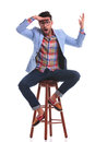 Casual man sitting while making a funny face Royalty Free Stock Photo