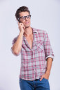 Casual man speaking on the phone young standing with a hand in his pocket and while looking away from camera gray Royalty Free Stock Images