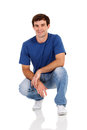 Casual man squatting happy on white background Royalty Free Stock Image