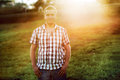 Casual man standing on the green grass in the park on the sunset young Stock Photos