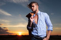 Casual man with sunset behind looks away young standing a hand in his pocket while the wind blows his hair and the sun sets him Royalty Free Stock Images