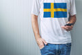 Casual man with Swedish flag on shirt using mobile phone Royalty Free Stock Photo