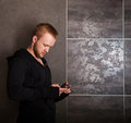 Casual man with touch screen phone near the grey wall Royalty Free Stock Photography