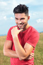 Casual man touches his chin young outdoor touching and smiling for the camera Royalty Free Stock Images