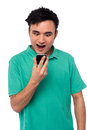 Casual man using his mobile phone excited young looking cellphone Stock Image