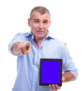 Casual middle aged man presents his tablet senior presenting a with blue screen and pointing towards the camera isolated on white Royalty Free Stock Images