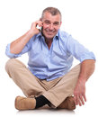 Casual middle aged man sits and chats on phone senior sitting the floor with his legs crossed speaking while smiling for the Stock Photos
