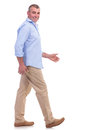 Casual middle aged man stepping forward side view of a senior walking and looking at the camera isolated on white background Royalty Free Stock Photography