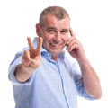 Casual middle aged man victory on the phone senior talking and showing sign while smiling for camera isolated white background Royalty Free Stock Image