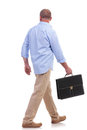 Casual middle aged man walks with suitcase full length picture of a senior walking away from the camera a in his hand isolated on Royalty Free Stock Images