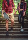 Casual moder young skateboarders couple posing on footway. Royalty Free Stock Photo