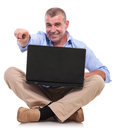 Casual old man sits with laptop and points senior sitting on the floor his legs crossed holds his while pointing at the camera a Stock Image