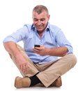 Casual old man sits and plays on phone senior sitting the floor with his legs crossed playing his isolated white background Stock Photography