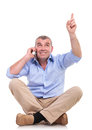 Casual old man sits and points up on phone senior sitting the floor with his legs crossed talking while pointing looking upwards Royalty Free Stock Photos