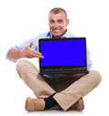Casual old man sits and presents his laptop senior sitting on the floor with legs crossed presenting with blue blank screen Royalty Free Stock Photo