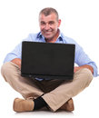 Casual old man sits and works at laptop senior sitting on the floor with his legs crossed holding his while smiling the camera Royalty Free Stock Image
