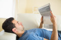 Casual peaceful man lying on couch reading newspaper in bright living room Royalty Free Stock Photos
