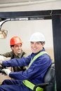 Casual portrait of two men in warehouse happy forklift driver with colleague at Stock Photography
