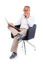 Casual senior man reading stock rates in newspaper sitting on a chair Royalty Free Stock Images