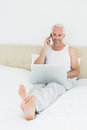 Casual smiling mature man using cellphone and laptop in bed portrait of a at home Stock Photos