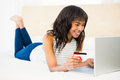 Casual smiling woman using laptop while holding a card Royalty Free Stock Photo