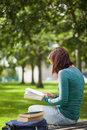 Casual student sitting on bench reading campus at college Royalty Free Stock Photos