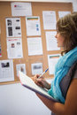 Casual student taking notes in front of notice board Royalty Free Stock Photo