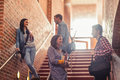 Casual students standing on stairs chatting in college Royalty Free Stock Images