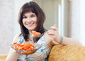 Casual woman eats veggie salad on sofa at home interior Royalty Free Stock Photo